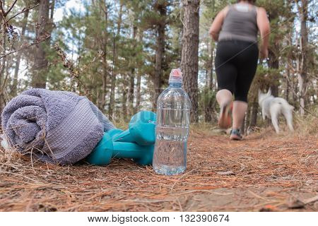 Overweight woman jogging on forest trail with waterbottle and towel in the foreground