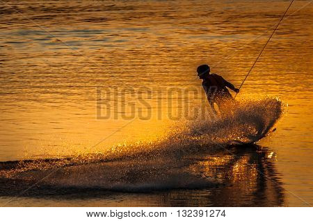 Silhouette of a wake boarder at sunset