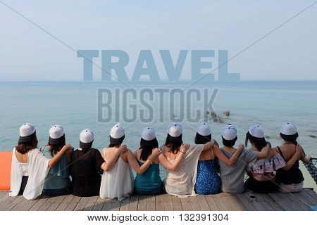 women friend group sit make arm hug hold around their friend's shoulder on wooden pier. They wear same design white and black color caps. looking at TRAVEL word on blue sea sky.
