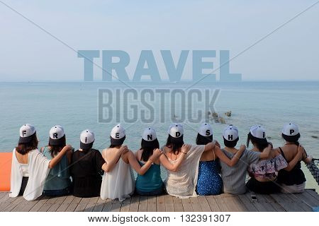 women friend group sit make arm hug hold around their friend's shoulder on wooden pier. They wear same design caps with FRIENDSHIP alphabets on each one.  looking at TRAVEL word on blue sea sky.