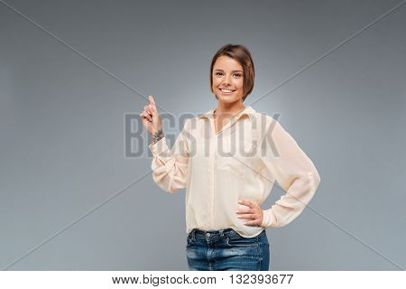 Portrait of a happy young woman pointing finger on gray background