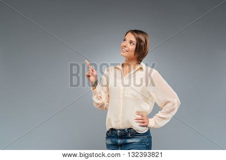 Portrait of a pretty young girl pointing finger up isolated on the gray background