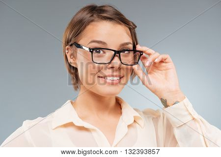Close-up portrait of a smart beautiful girl touching her glasses isolated on the gray background