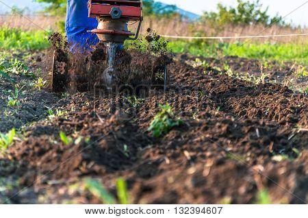 Man using a power tiller on a farm