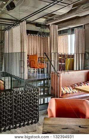 Charming zone on a metal elevation with stairs on the window background in a mexican restaurant. The zone framed with metal lattices and curtains. In the zone there is a motley sofa with a wooden table, multi-colored chairs and a wrought lamp over them.