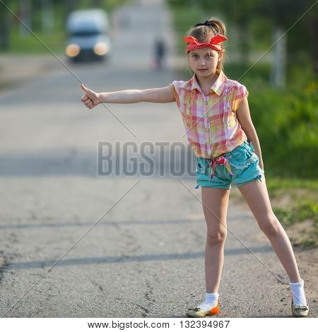 Little funny girl hitchhiking on the road.