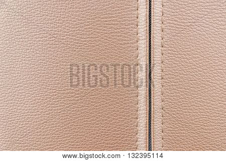 the leather texture background in the light brown tone.close up of the leather texture with the zipper