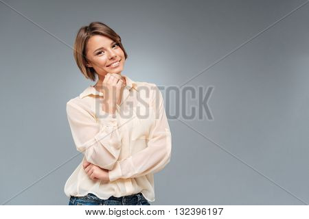 Young cute woman thinking about something on the gray background grey background