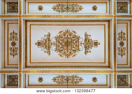 Antique and baroque ceiling decorated with golden meander ornament