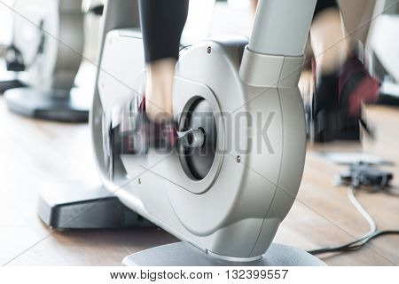 Detail of a woman working out on a stationary bike. Motion effect