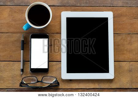 Office stuff with blank screen tablet pen smartphone eyeglasses and cup of coffee . Flat lay photo.Top view