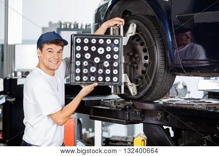 Mechanic Using Wheel Aligner On Car