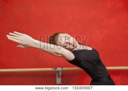 Ballerina Stretching Against Red Wall