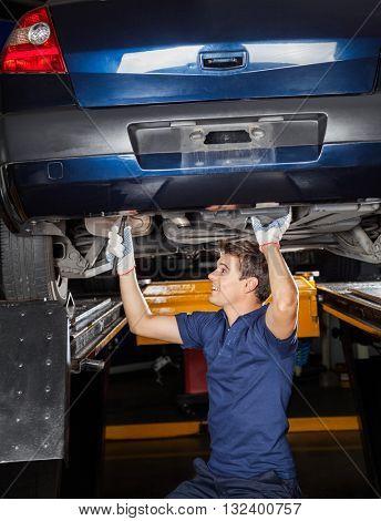 Mechanic Repairing Lifted Car