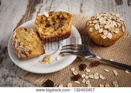 Fresh muffins with oatmeal baked with wholemeal flour on white plate and fork concept of delicious healthy dessert or snack