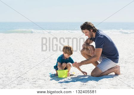Father and son playing with toys at beach. Family of father and son enjoying summer vacation at beach. Father helping son fill basket with sand.