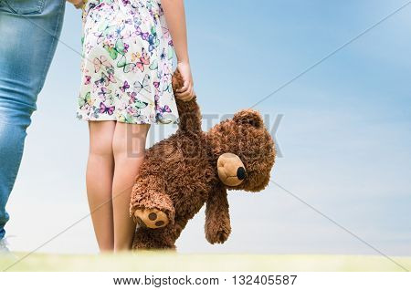 Rear view of little girl looking her future with her father. Close up of hands of a female child holding a teddy bear. Girl standing holding a brown furry teddy bear.