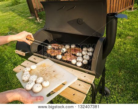 Red meat chops and champignons being placed on barbecue