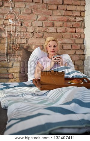 Daydreaming young woman drinking tea in bed in the morning.