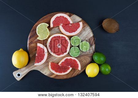 Slices Of Citrus Fruits On Chopping Board  With Whole Lemon And Lime Top View With Copy Space