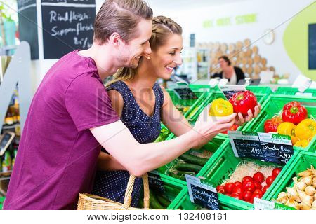 Couple selecting paprika while grocery shopping in organic supermarket