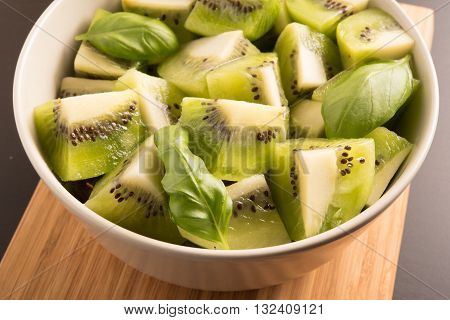 Kiwi fruit sliced segments with basil leaves in a round bowl on the wooden panel