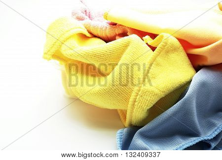 Closeup pile of colorful microfiber towel/cloth for car wipe. Focus on yellow towel. Space for texts. Isolated on white background.