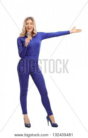 Full length portrait of a woman in a blue one-piece racing suit speaking on microphone and pointing with her hand to the right