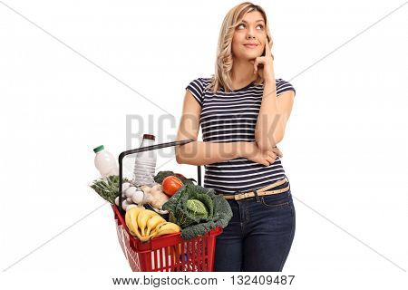 Pensive young woman holding a shopping basket isolated on white background