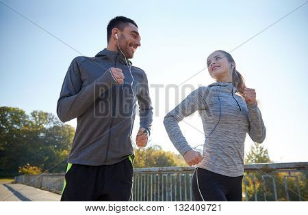 fitness, sport, people and lifestyle concept - happy couple with earphones running outdoors