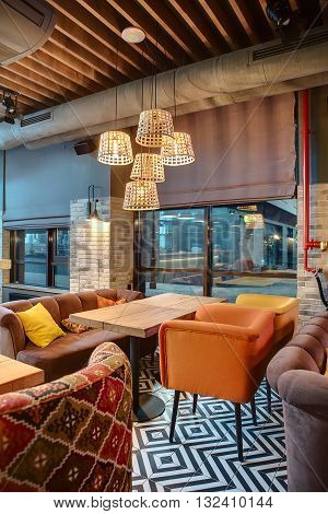 Nice room in a mexican restaurant in a loft style. There are several wooden tables with multi-colored chairs and sofas. On the sofas there are color pillows. Over the tables there are glowing wicker lampshades. On the back wall there are windows