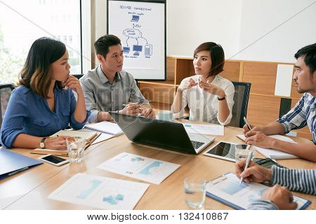 Coworkers discussing strategy of company development in office