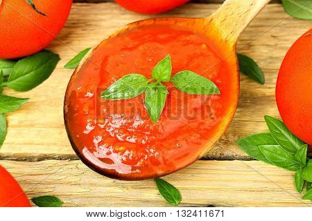 wooden ladle with tomato sauce on wooden surface