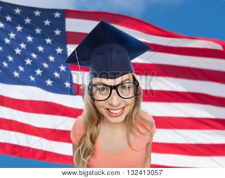 people, graduation and national education concept - smiling young student woman in mortarboard and eyeglasses over american flag background
