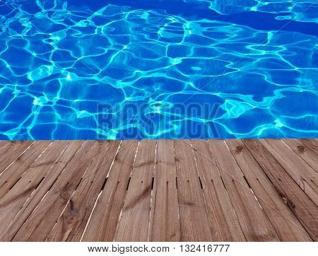 Old wooden floor and blue water in swimming pool.
