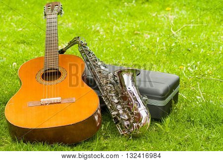 Beautiful golden saxophone and acoustic guitar lying across black instumental case on grassy surface.