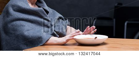 Panoramic picture of a woman sitting at the table and refusing to eat a soup