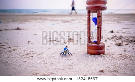 Image Of Mini Figure Dolls Biker And Sandglass On The Beach
