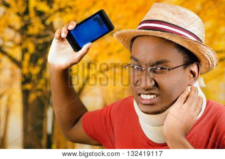 Injured black hispanic male wearing neck brace, glasses and hat, holding cell phone making painful facial expression, yellow abstract background.