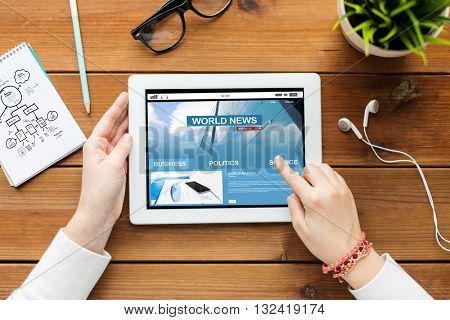 business, education, technology, people and mass media concept - close up of woman with world news on tablet pc computer screen on wooden table