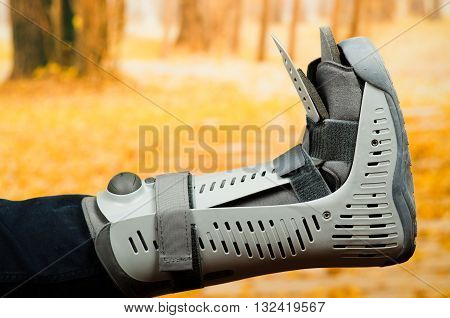 Injured foot wearing extensive grey plastic protection case in front of autumn background.