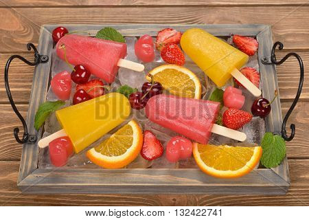 Frozen fruit juice popsicles on a brown background