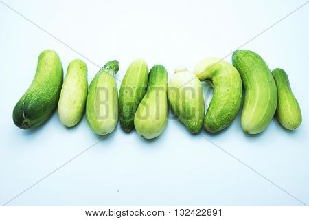 Green cucumbers with incomplete shape, isolated on blue-white background.