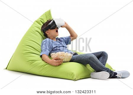 Amazed little boy looking in VR goggles and eating popcorn seated on a beanbag isolated on white background
