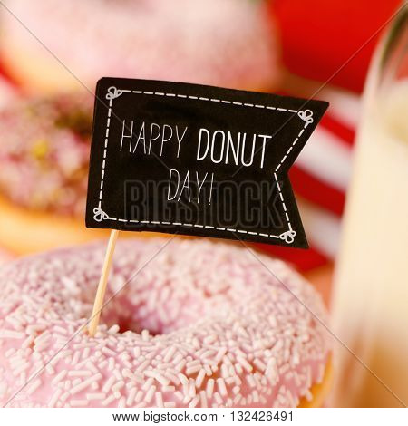 closeup of a black flag-shaped signboard with the text happy donut day in an appetizing donut coated with a pink frosting and white sprinkles