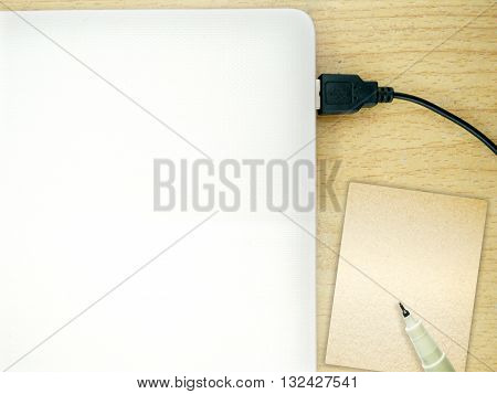 Laptop on wooden desk with note book