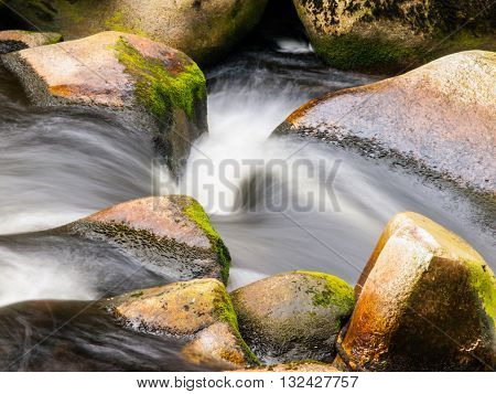 Blurred river stream detail of wild rocky mountain river. Silky effect. Motion rendition effect. Slow shutter speed effect. Long exposure effect.