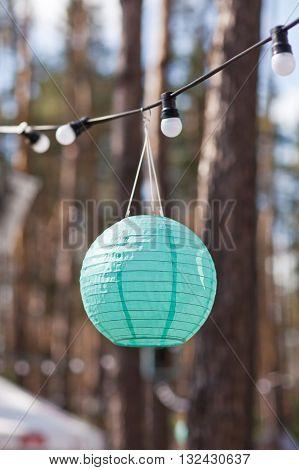 Green paper lantern on a garland from light bulbs.