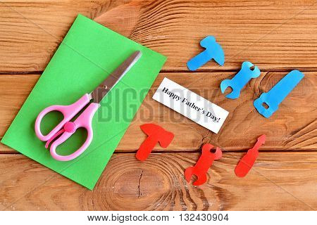 Hammer, wrench, saw, tools cut from colored paper. Scissors. Green paper sheet. Sheet with words Happy father's day. Set for handmade greeting card. Simple paper cutting art and craft idea for kids.