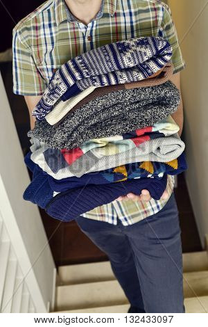 closeup of a young man wearing a short sleeved shirt carrying a pile of different folded sweaters